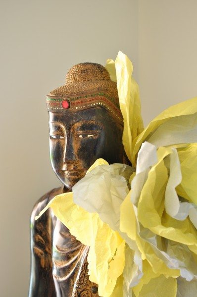 Grey and yellow pom pom tied to a buddha at my grey and yellow baby shower