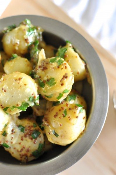 Vegan potato salad made with olive oil and grain mustard in a bowl sprinkled with parsley